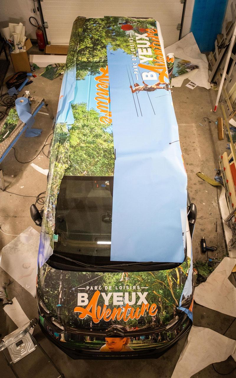 Pose d'un adhésif pour un marquage total covering sur un véhicule Bayeux aventure
